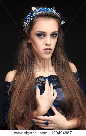 terrible girl with a long face in the diadem. witch conjures.
