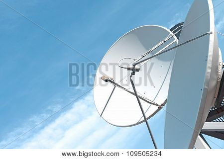 Satellite dish and antenna on blue sky background poster