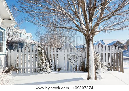A garden gate leading into a back yard garden is decorated with a Christmas wreath all covered in snow.