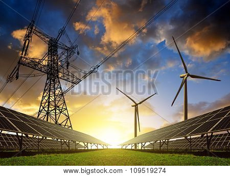 Solar panels with wind turbines and electricity pylon at sunset.