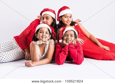 4 indian teenagers with red cloths and red santa hat, lying on white floor for photo, isolated on wh