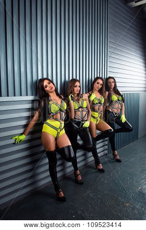 Four Confident Pretty Sexy Girls In Stage Costumes Standing At The Wall