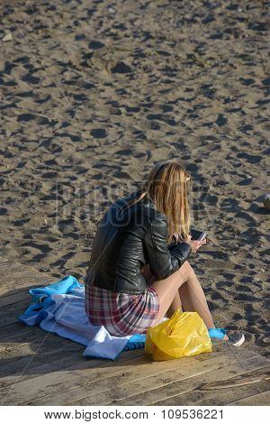 Young Woman Is Sitting With Smartphone On The Beach.