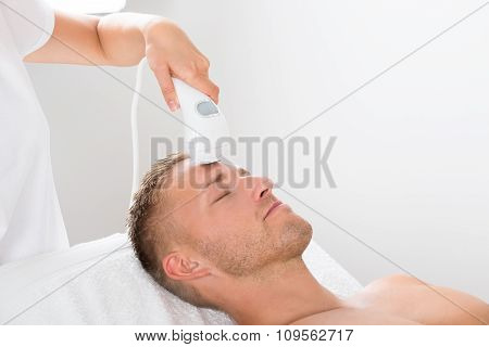 Young Man Receiving Laser Hair Removal Treatment At Beauty Center poster