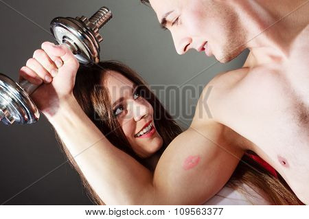 Couple Muscular Man And Girl Admiring His Strength.