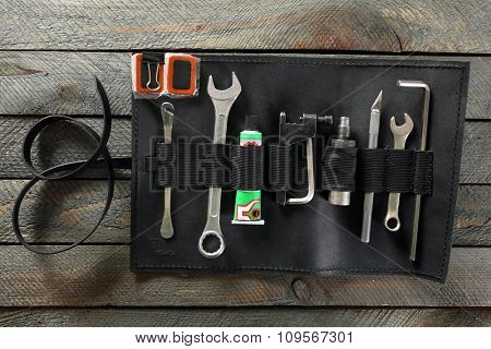Leather case with instruments on wooden background