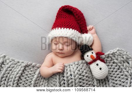 Newborn Baby Boy With Santa Hat And Snowman Plush Toy