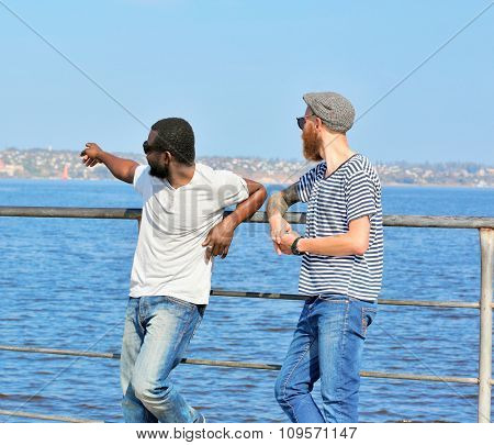 Two young men talking on the riverside
