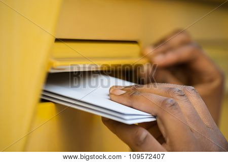 Person's Hand Inserting Letter In Mailbox