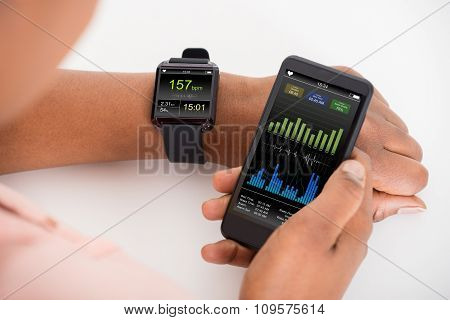 Hand With Mobile And Smartwatch Showing Heartbeat Rate