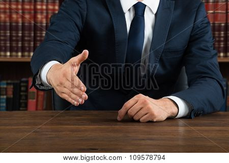 Lawyer Offering Handshake At Desk In Courtroom