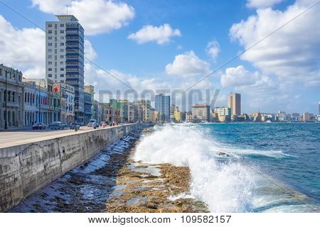 The skyline of Havana with waves crashing on the Malecon seawall