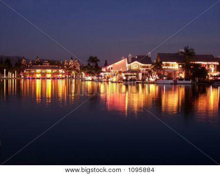 Christmas Lights On Lake At Dusk