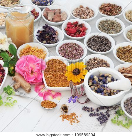 Natural flower and herb selection used in herbal medicine with pollen and  honey bee over distressed wooden background.