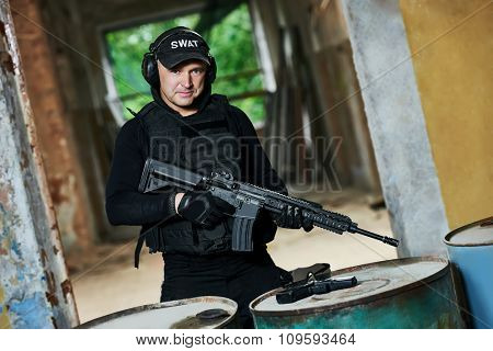 Military industry. Special forces or anti-terrorist police soldier portrait,  private contractor armed with assault rifle ready to attack during clean-up operation, mission