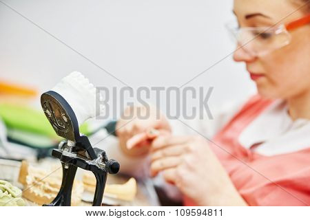 Female dental technician working with tooth dentures at prosthesis laboratory. Focus on articulator