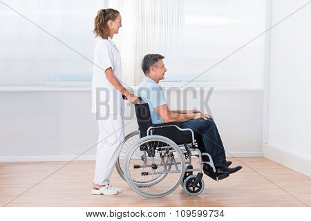 Doctor Pushing Disabled Patient On The Wheelchair