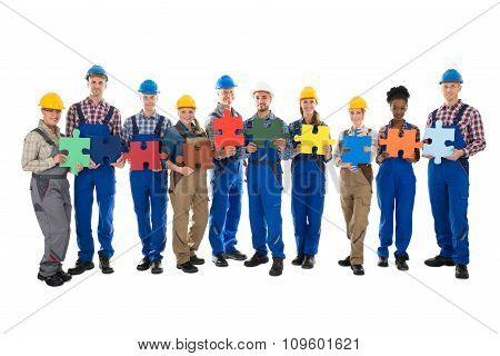 Confident Construction Workers Holding Jigsaw Pieces In Row