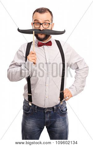 Vertical shot of a young happy hipster holding a fake mustache on his face and looking at the camera isolated on white background