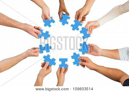 Creative Business People Holding Blue Jigsaw Pieces
