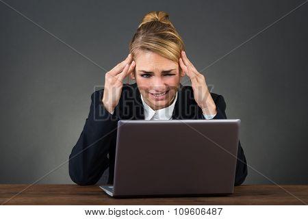 Businesswoman Suffering From Headache At Desk