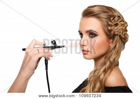 portrait of a beautiful young blonde woman on a light background. there is hand with aerograph makin