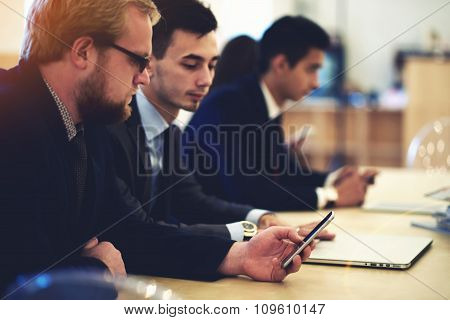 Skilled man manager reading something on smart phone while sitting with staff in office interior