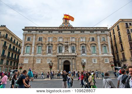BARCELONA, SPAIN - MAY 01: Large Number of Pedestrians Walking Past Exterior of Palau de la Generalitat de Catalunya, a Medieval Building Housing Government Offices in Barcelona, Spain. May 01, 2015