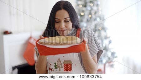 Attractive young woman baking tarts for Xmas standing in front of the Christmas tree savoring the aroma of a freshly baked pie