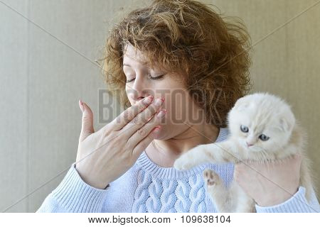 woman with allergy is holding  kitten