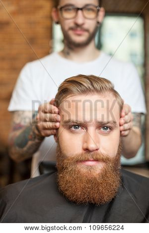 Skillful male barber is serving his client