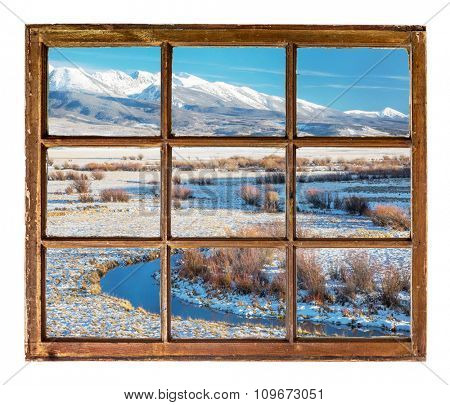 travel concept or a greeting card from Colorado - river valley and snowy mountains  as seen  through vintage, grunge, sash window with dirty glass