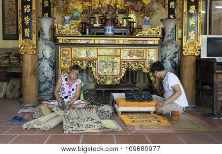 Senior craftsmen making printed painting artwork in traditional way