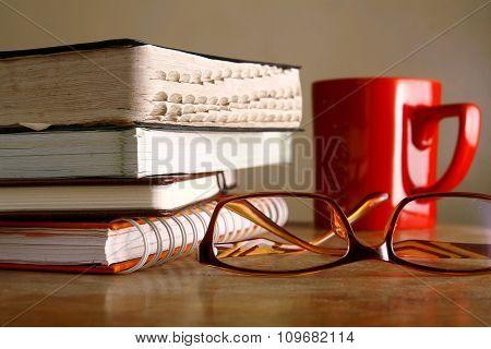 Eyeglasses, coffee mug and pile of books