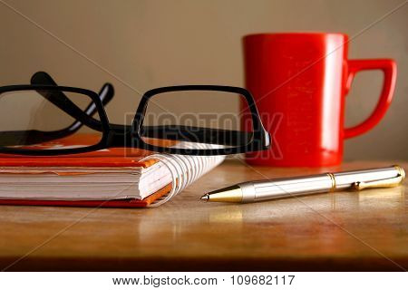 Eyeglasses, coffee mug, notebook and a pen