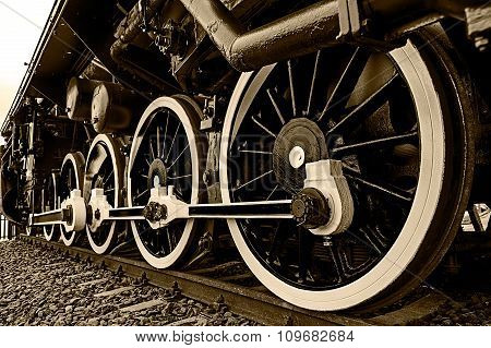 Old german steam locomotive in a museum. Detail and close up of huge wheels. Sepia processing. poster