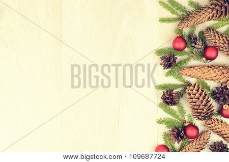 Branches Of Spruce, Red Balls And Fir Cones On A Wooden Background