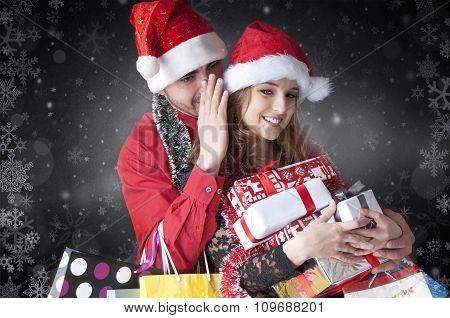 Girl whispering a secret boyfriend's ear.Happy christmas couple gossiping.Snowy card. poster