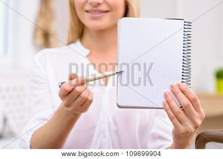 Young woman showing her notebook.