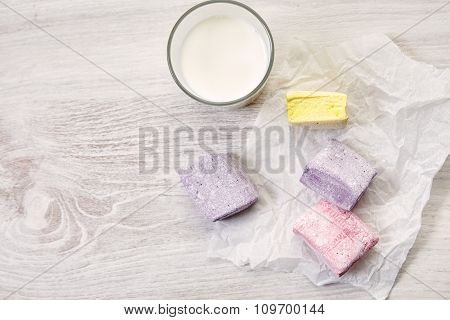 Some Pastel Colored Marshmallows Top View With Glass Of Milk On Craft Paper