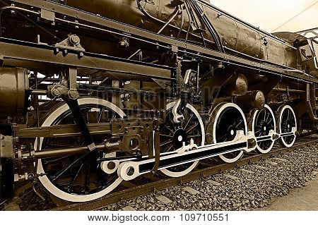 Old german steam locomotive built in 1940 in a museum. The heaviest locomotive 85 tons that circulated in Romania during the Second World War. Detail and close up of huge wheels. Sepia processing. poster
