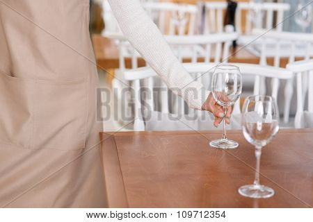 Waitress is putting water glasses on the tables.