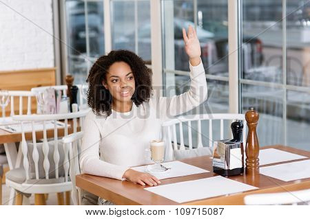 Customer is waving to the waiter.