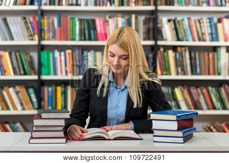 Blonde Young Girl Sitting At A Desk In The Library With Piles Of Book On Both Sides Of The Desk Rea