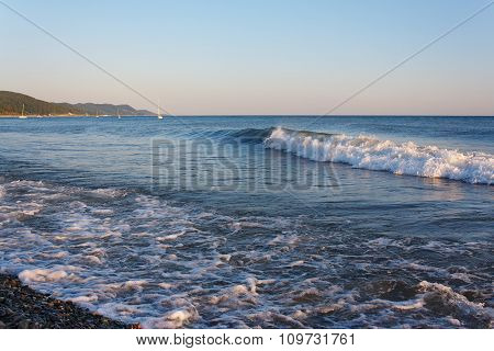 Tranquil surf on the beach against the backdrop of mountainous coast