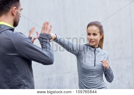 fitness, sport, martial arts, self-defense and people concept - happy woman with personal trainer working out strike outdoors