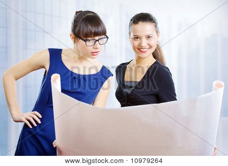 Two Young Women Examining A Drawing