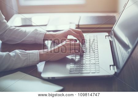 Woman working in home office hand on keyboard close up