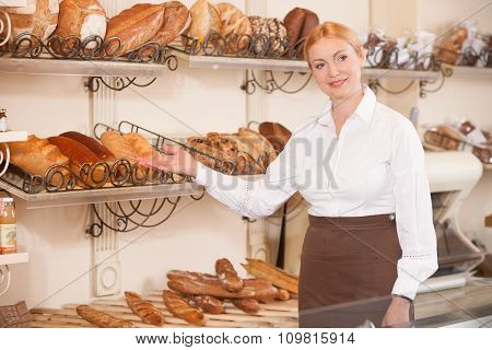 Cheerful female baker is inviting to her shop