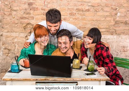 Group Of Young Hipster Best Friends With Computer In Urban Alternative Studio - Friendship Concept